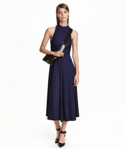 Mörkblå. En vadlång klänning i ribbad trikå. Klänningen är ärmlös och smalt  skuren upptill. Dold dragkedja bak och tryckknappar i nacken. Avskuren i  midjan 83a4c45418a51