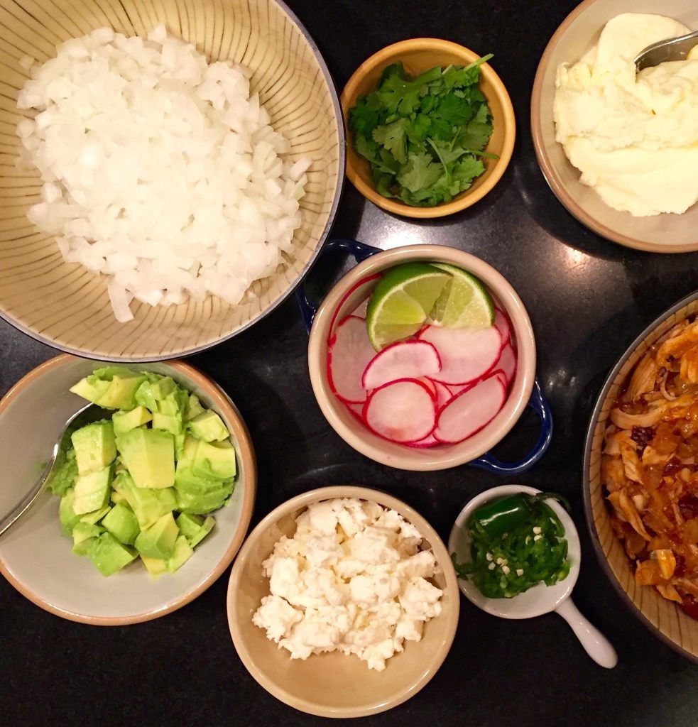 Toppings for tacos in small bowls.