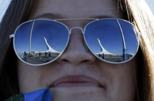 The Olympic flame is reflected in glasses worn by a volunteer at the Olympic Park during the 2014 Sochi Winter Olympics, February 13, 2014.