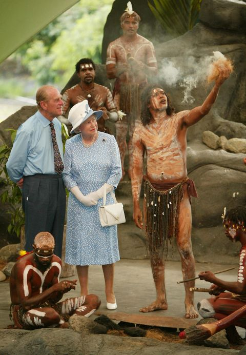 Queen Elizabeth II (C) and her husband Prince Philip (L) watch Tjapukai Aborigines light a ceremonial fire during a cultural performance near Cairns, 01 March 2002. The British monarch, who is in Australia on the final leg of her golden jubilee tour, will officially open the Commonwealth Heads of Government Meeting (CHOGM) in Coolum on 02 March. (Photo credit should read TORSTEN BLACKWOOD/AFP/GettyImages)
