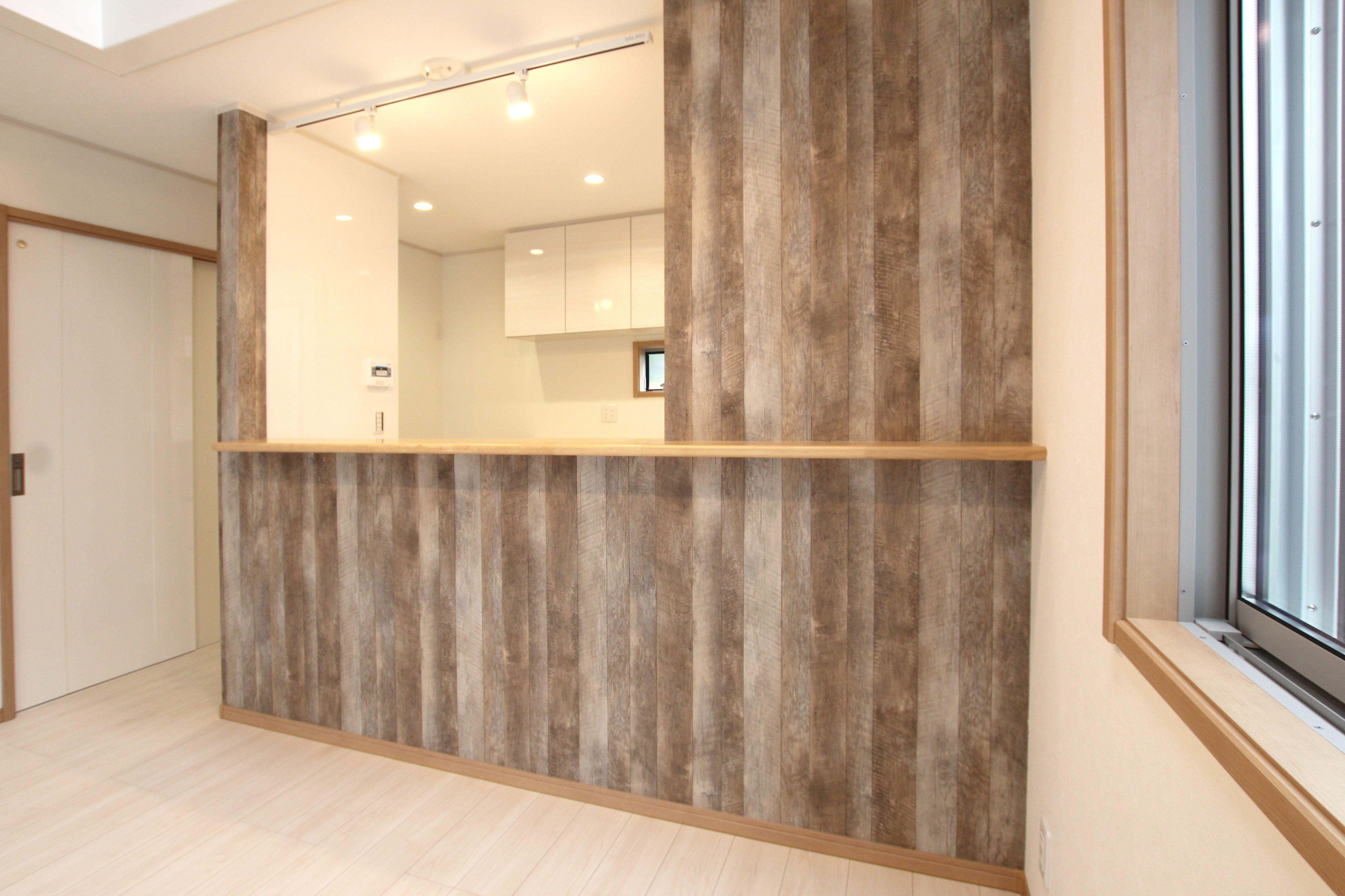 木目調のヴィンテージ風クロスが印象的なキッチンカウンター スモーキーな色調を使用し ブルックリンスタイルを取り入れました できたてのお料理をカウンターから配膳出来る スマートな家事動線が特徴です ブルックリンスタイル 木目調クロス ヴィンテージ風