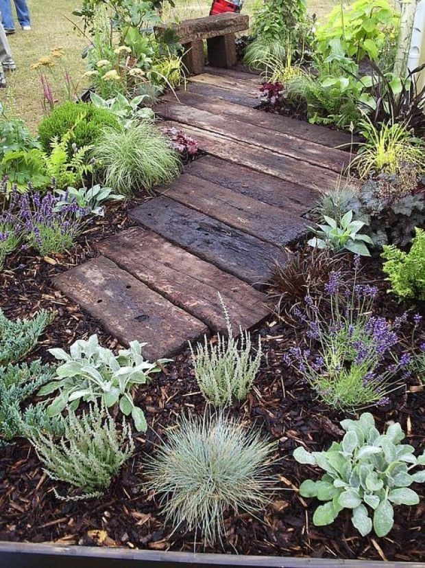 Photo of garden path- railway sleepers. we could surround with mulch like this and make a…