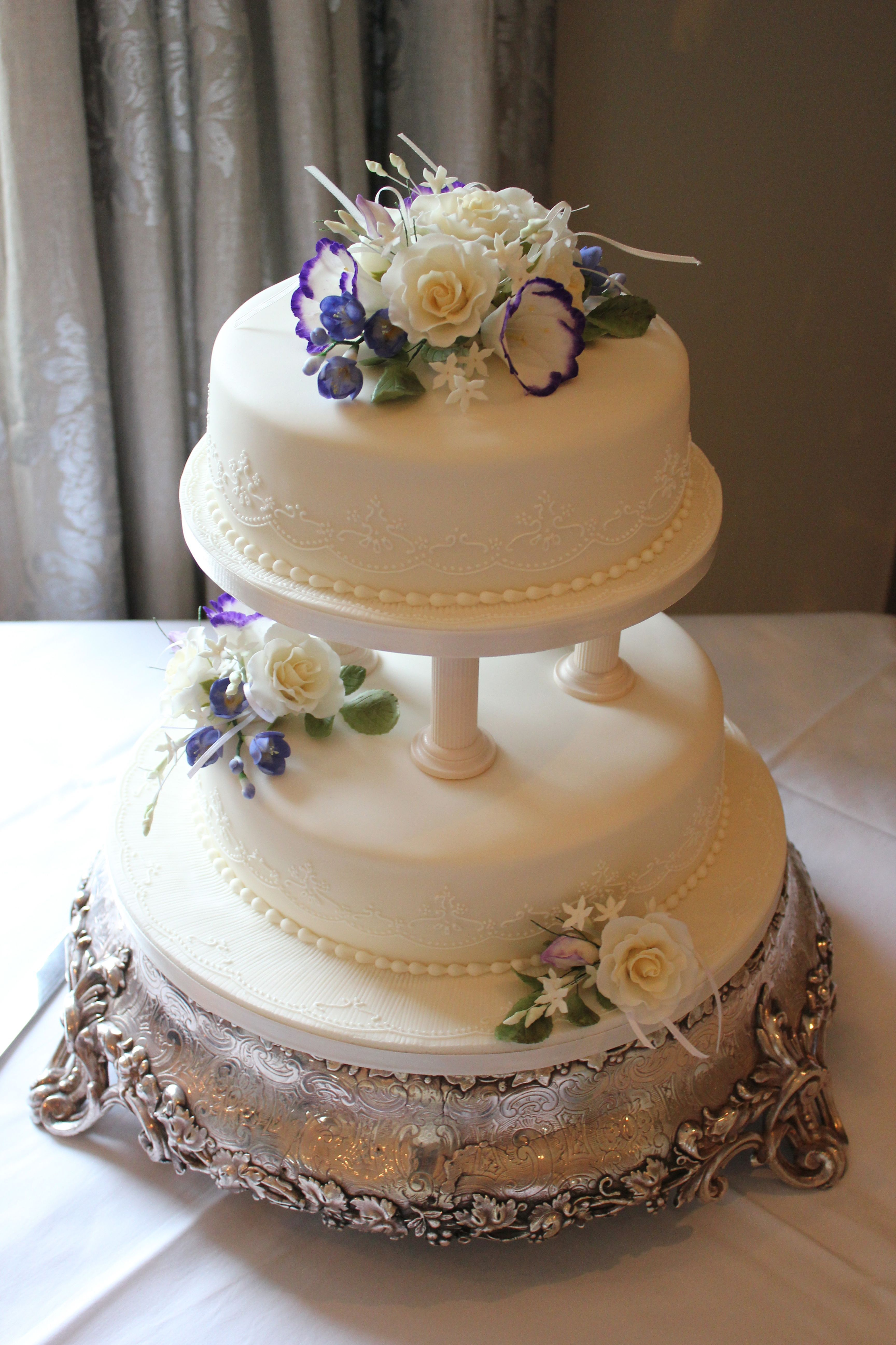 A Two Tier Cake With Pillars And Icing Flowers To Create This