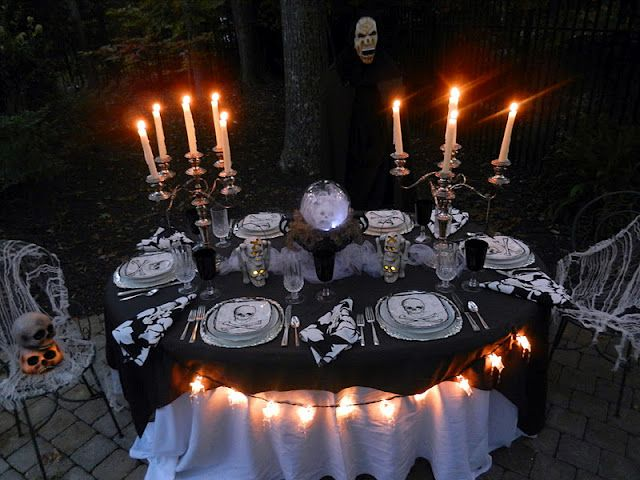 The table has been set with the finest china and silver Outdoor - halloween table setting ideas