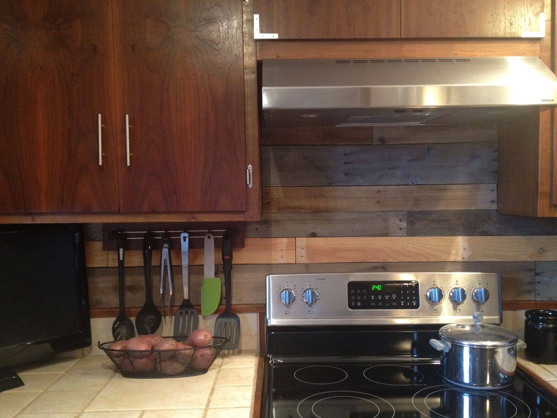 finished pallet wood backsplash behind stove