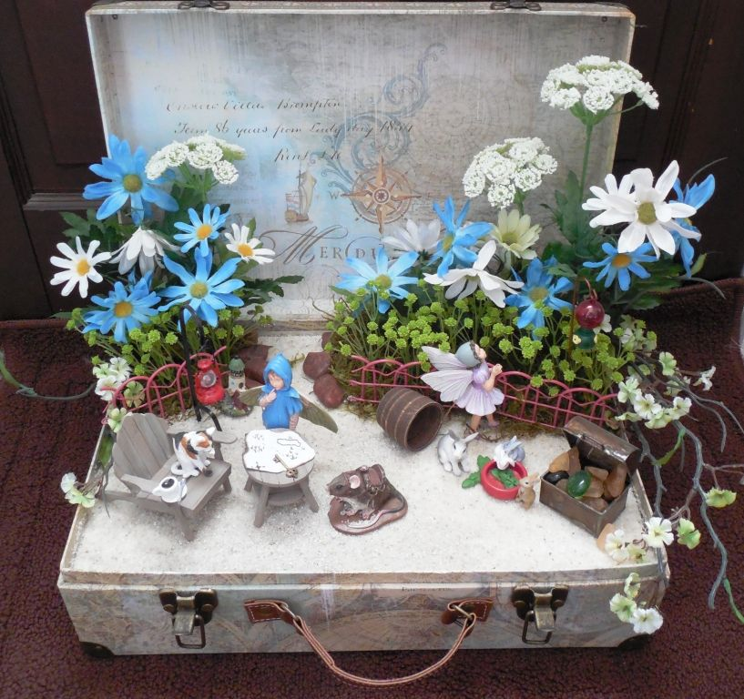 I made this indoor fairy garden using a 'suit case' bought at a craft store.  Because I used a suit case the theme of this garden is Adventure.  The blue fairy is looking at a treasure map, there is a treasure chest and a mouse saddled up and ready to go!