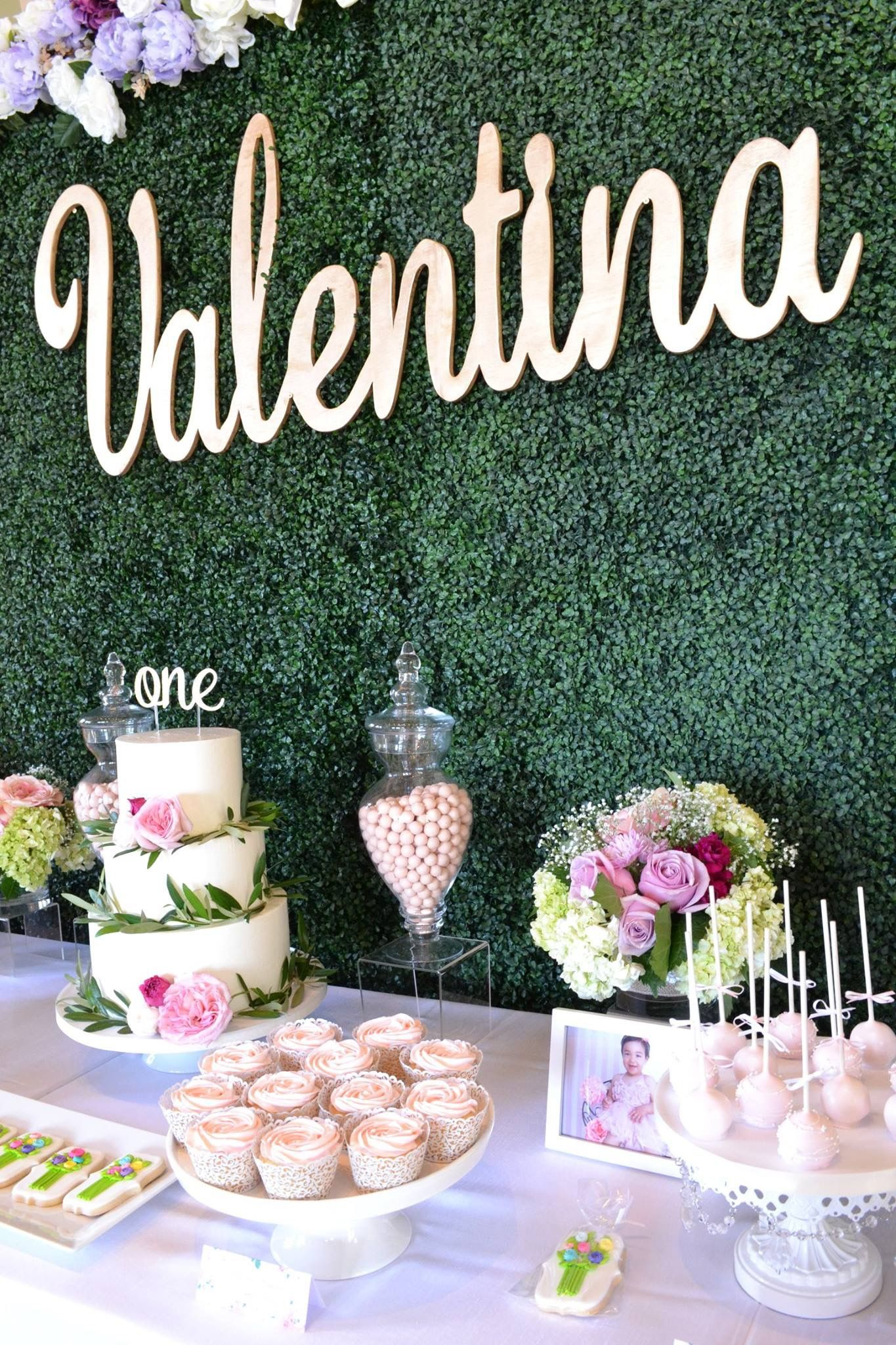garden party with hedge wall background and gold name sign grass