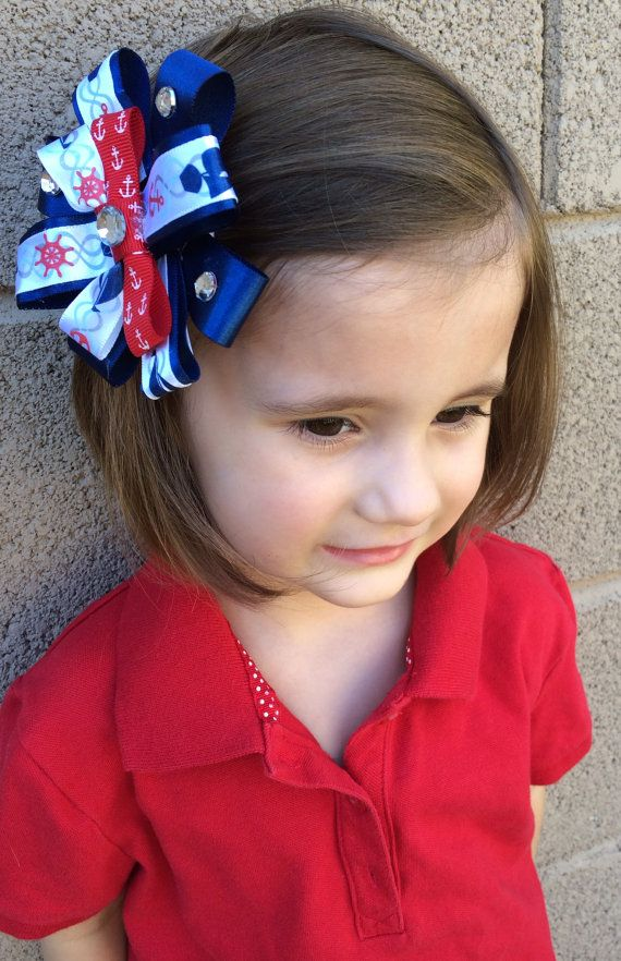 Adorable navy flower satin ribbon bow with red anchor ribbon in the middle and a sparkling rhinestones to accent. Alligator clip on back. Pairs