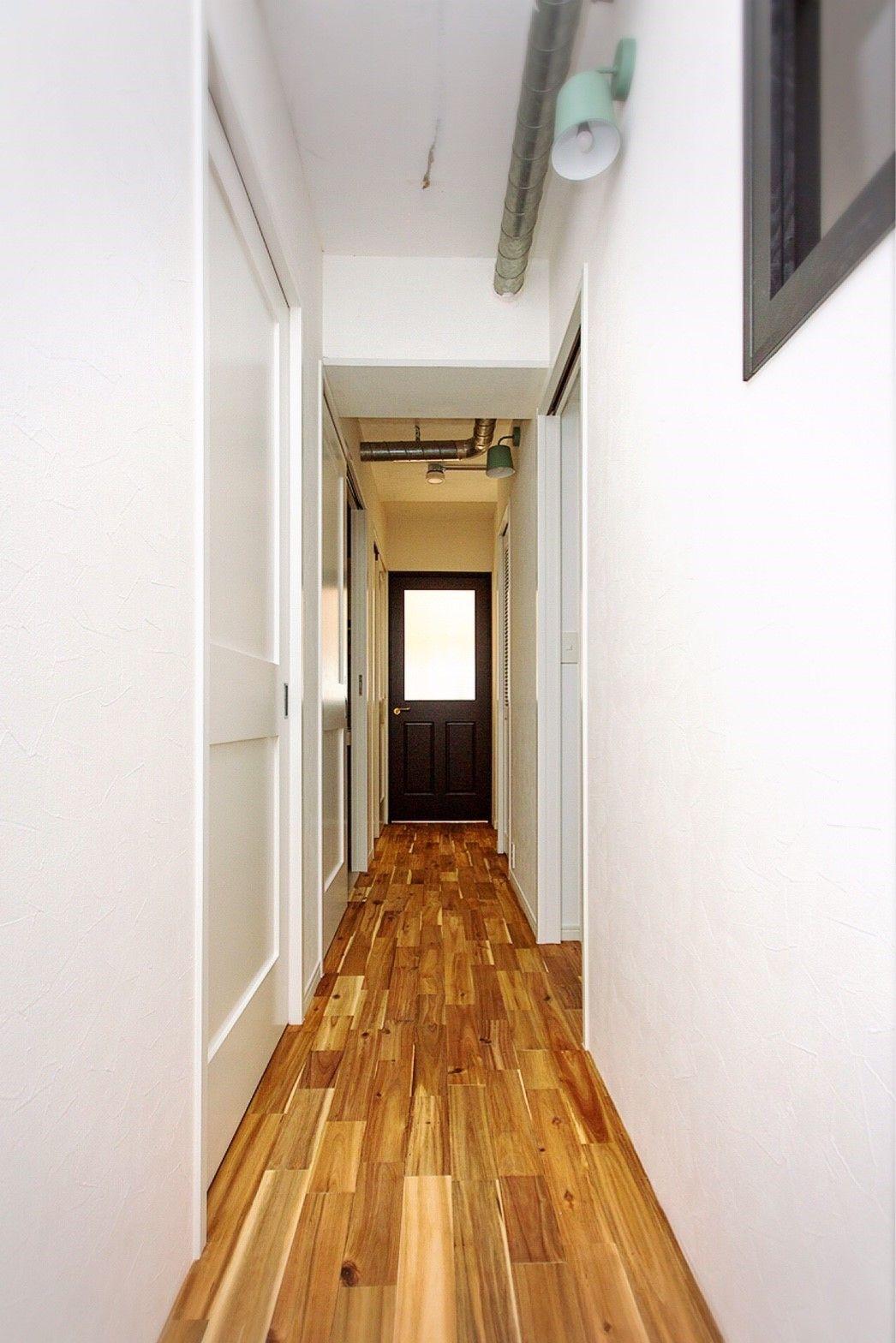 木のフローリングがおしゃれな廊下にポイントカラーのドア アレンジ