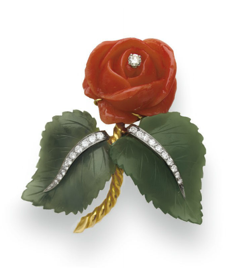 A CORAL, NEPHRITE AND DIAMOND FLOWER BROOCH, BY DAVID WEBB  Designed as a carved coral flower with a circular-cut diamond pistil, extending two carved nephrite leaves, enhanced by graduated circular-cut diamond veining, to the sculpted gold stem, mounted in yellow and white gold, circa 1957