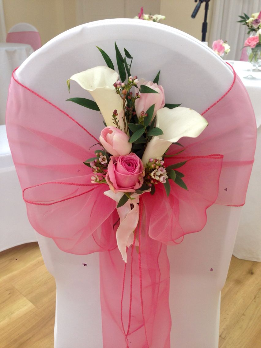 Coral organza sashes on white stretch chair covers with a floral ...