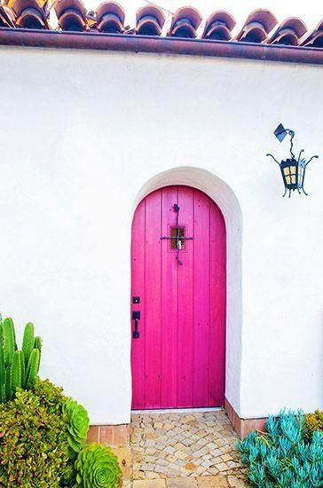 This pink arched wood front door is so welcoming.