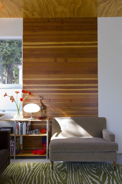 A strip of horizontal wood paneling gives this room interest, warmth and major design cachet. And note the windows: no coverings.