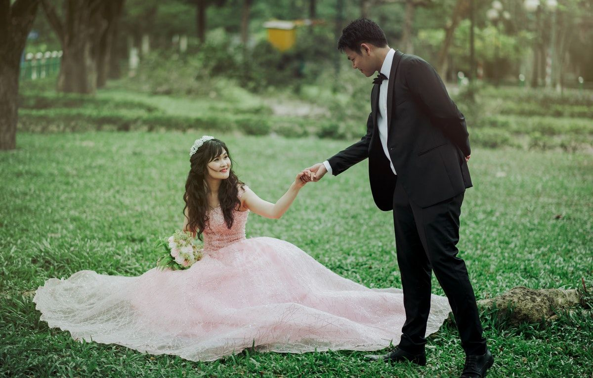Man in piece suit holding woman in peachcolored wedding gown