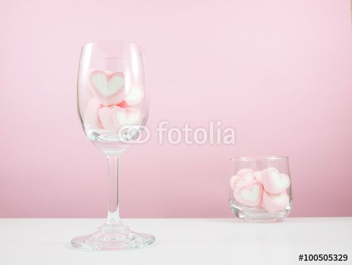 The lovely pink heart marshmallows in wine glass and small round glass on white table for Valentine's day.