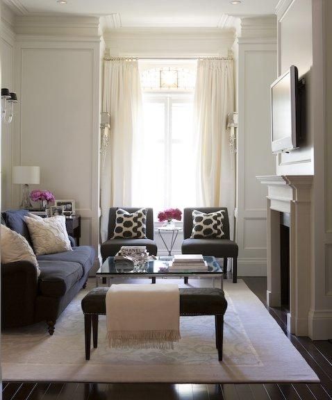 Chic living room design with ivory paneled walls  silk drapes lucite sconces