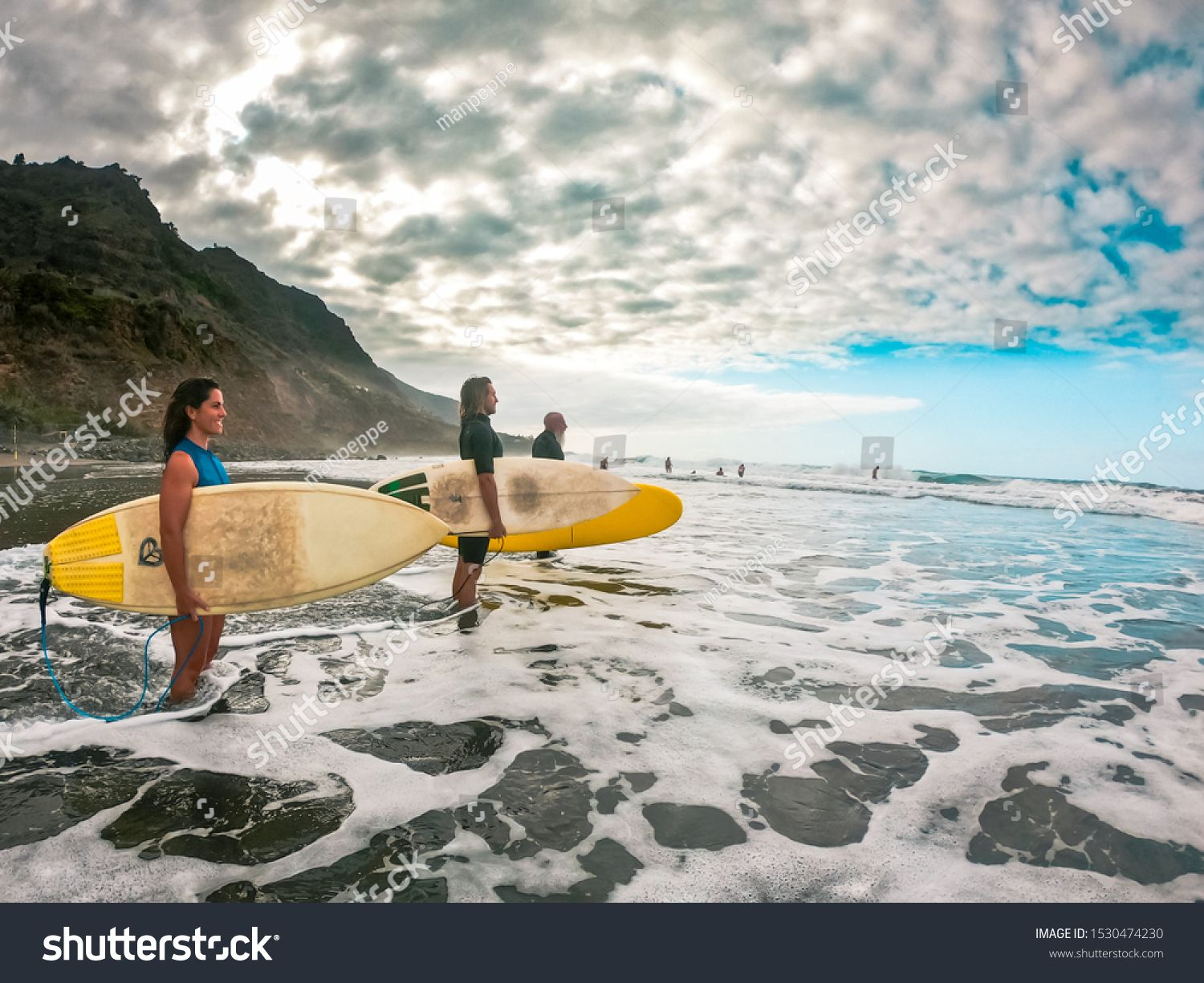 Men and a woman are standing with a surfboard in hand by