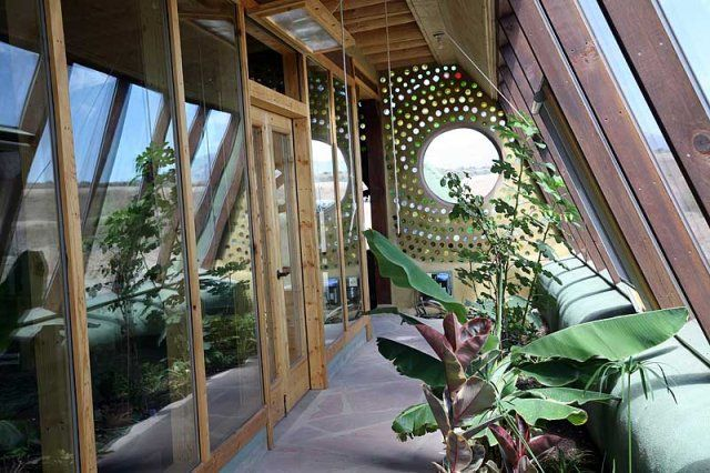 Earthship. That wall is made of mud and glass bottles!  How beautiful is that?!