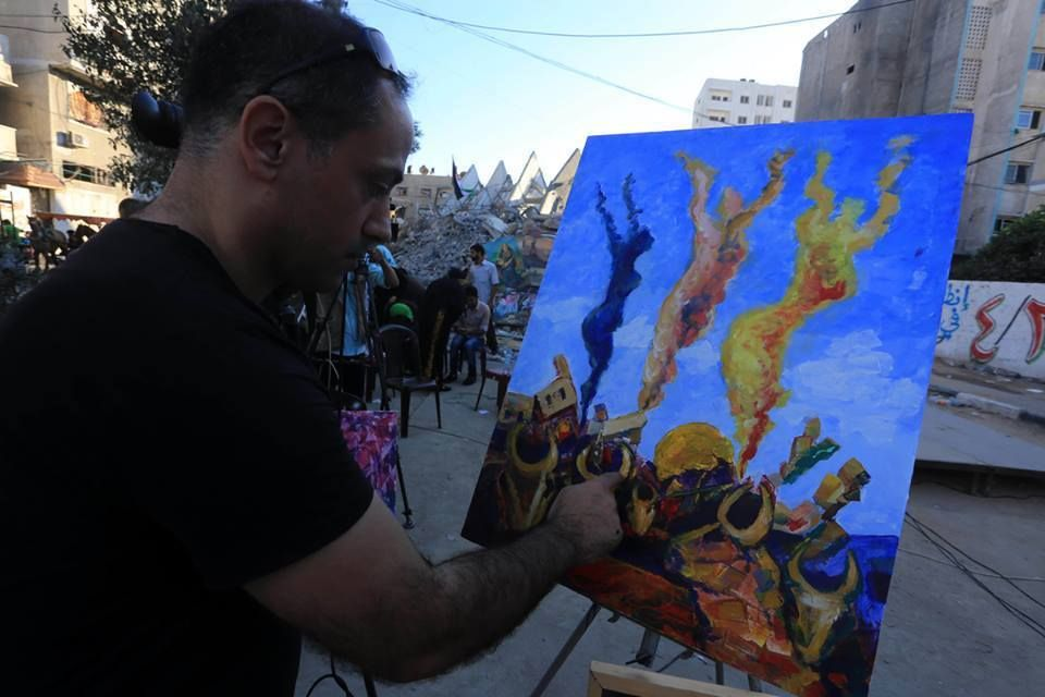 Palestinian artists do paintings over the rubble of Al-Basha building that was shelled and leveled by Israeli warplanes during Israel's 51-day assault against Gaza Strip