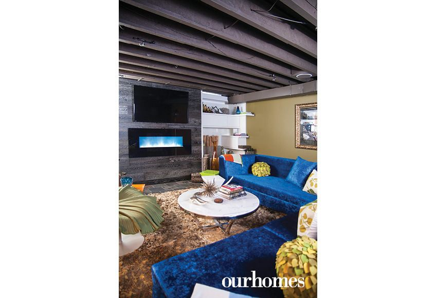 """The sapphire blue sofa in the lower level lounge is a brilliant counterpoint to the rustic beams. The fireplace surround was fashioned from reclaimed wood and gives the room a warm, organic feeling, as does the slate floor.   See more of this home in """"Homeowner's Design Choices Reflect Mischievous, Confident Style"""" from OUR HOMES Windsor Fall 2016 http://www.ourhomes.ca/articles/build/article/homeowners-design-choices-reflect-mischievous-confident-style"""