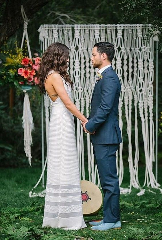 bohemian ceremony altar with a floor-grazing macrame backdrop and hanging potted flower arrangements / http://www.deerpearlflowers.com/boho-macrame-knotted-wedding-decor-ideas/
