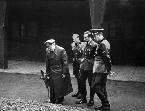 Adolf Hitler, Blondi, Karl Brandt, Albert Bormann and Otto Günsche, at the Wolfsschanze, 20 July 1944.