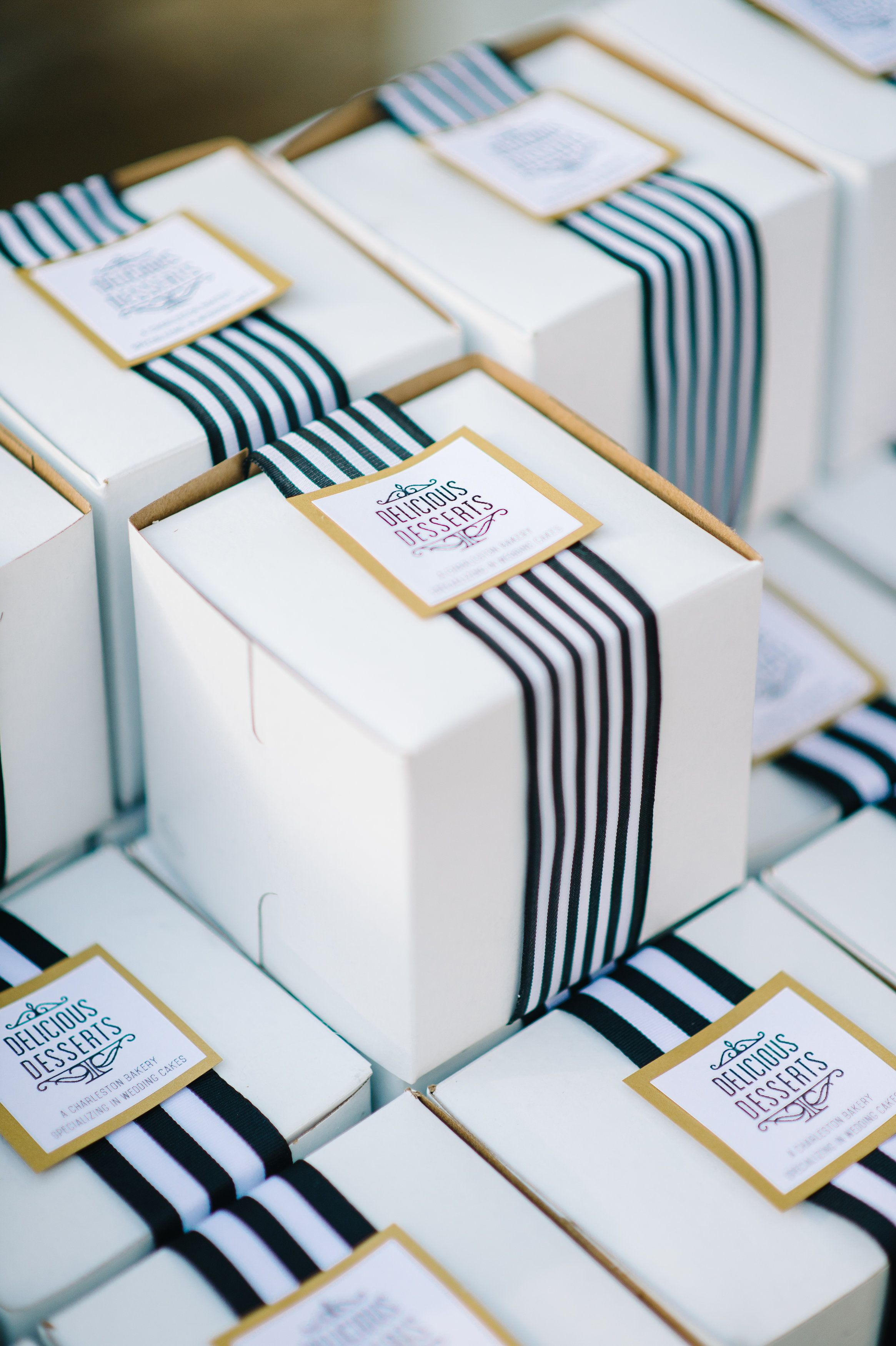 White cake boxes with black white and gold striped ribbon, wedding ...