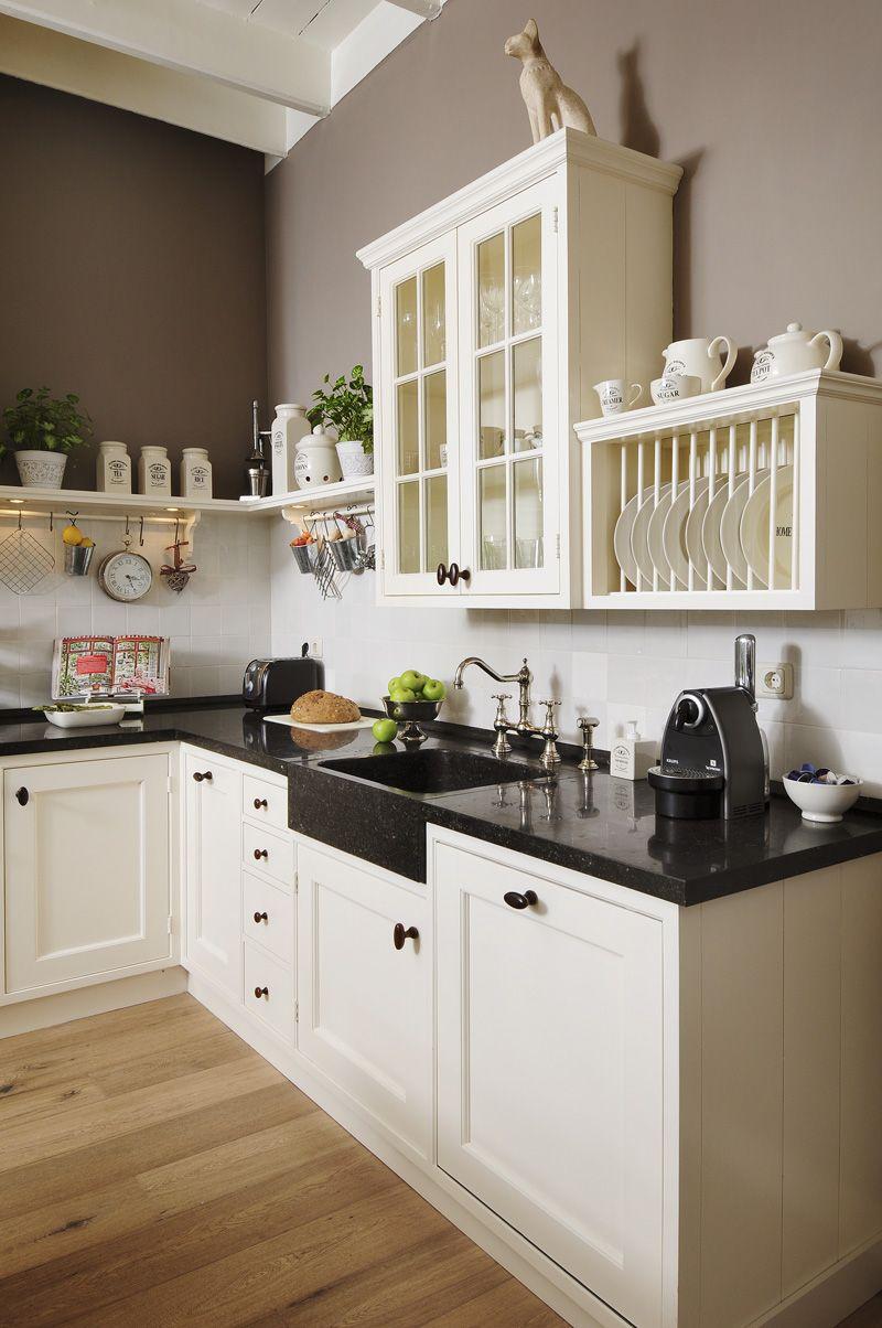 Klassieke keuken met glazen kasten en schiereiland. de bovenkasten ...