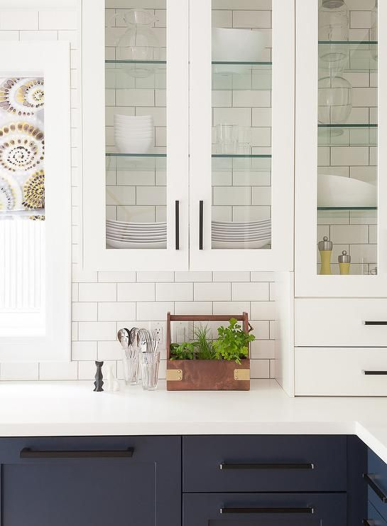 Glass Front White Kitchen Cabinets Accented With Glass Shelves Are Fixed  Against White Subway Backsplash Tiles