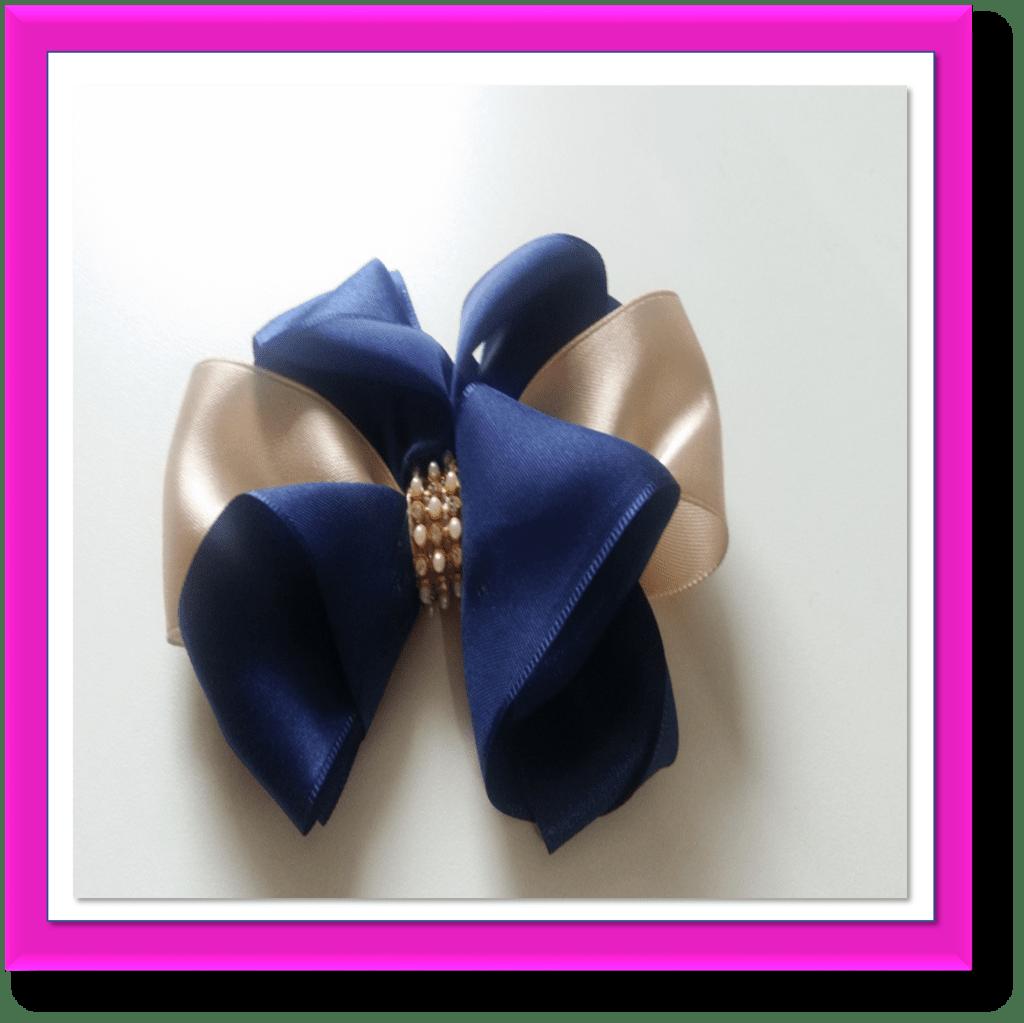 lao de fita de cetim duas cores decorado com strass e afixado em bico de pato