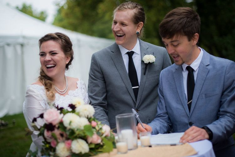 having your friend be the wedding officiant signing the marriage license groom in gray