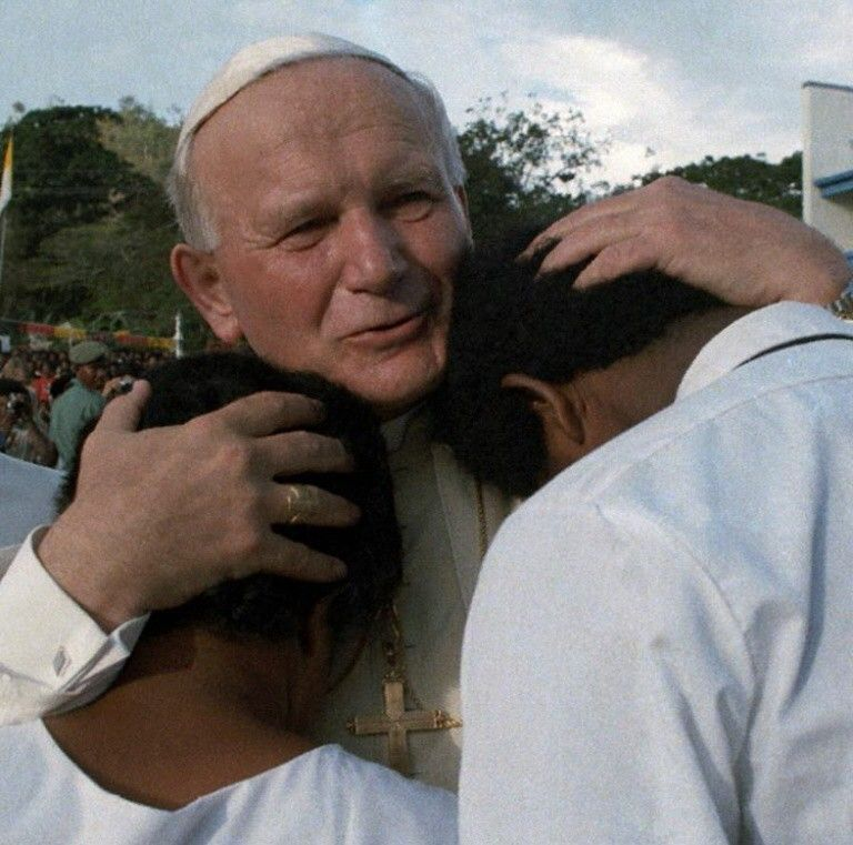 Pope John Paul II embraces children at the Vatican