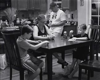 "A family is gathered around the kitchen table but distracted from one another by invisible mobile devices. ""l'm hoping there are going to be some families that see this work and they but a basket by the door and the phones go in it before they all sit down to dinner"""