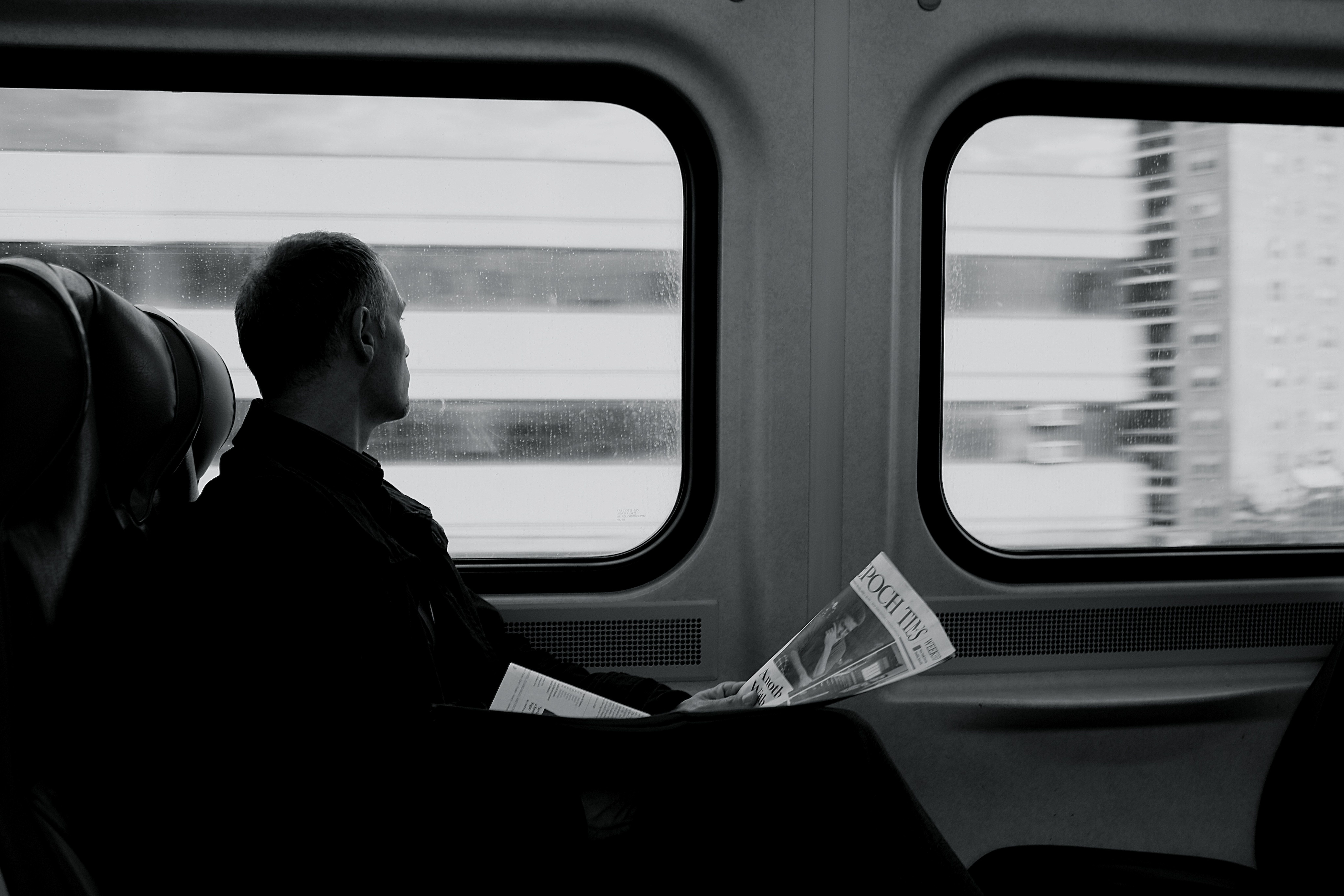 Black and white shot man with newspaper looking out metro carriage