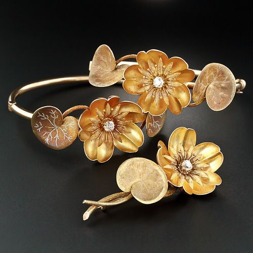 A marvelous and poetic rarity, this suite of brooch and matched bracelets hail from the Art Nouveau or Arts and Crafts movement, circa 1900, and were inspired by the arts of Japan and in particular the revered waterlily, the flower that in the same time period became something of an obsession for the French painter Claude Monet. Crafted in rosy 14 karat gold, with a velvety high-carat gold bloom on the flowers and patinated leaves with white and rose gold veining
