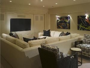 Cream sectional sofa with black throw pillows! Creates great ambiance with recessed lighting! Blue and cream media living room space colors.