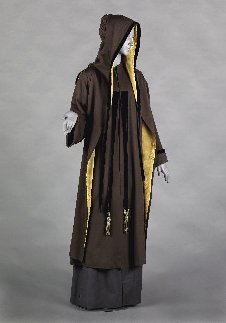 Capuchon Paul Poiret 1907 Capuchon à pèlerine, amovible, longs pans, galons de velours en bordure. Fond monté à fronces.Drap de laine marron, galon en velours bleu marine, doublure en pongé de soie jaune.