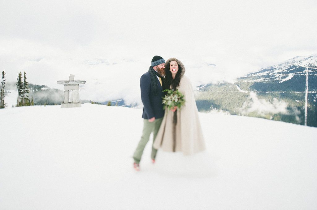 bride and groom in snow with inukshuk photograph by Whistler Wedding Collective