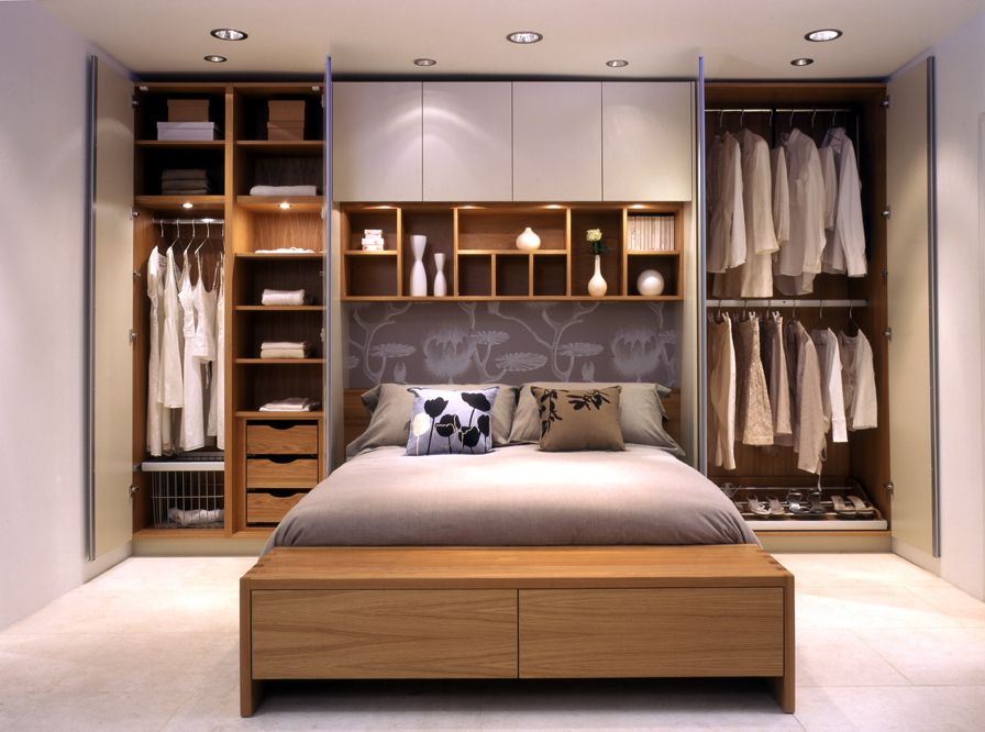 wardrobes on either side of the bed and with long white curtains covering