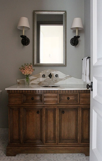 Traditional Powder Room With Gray Walls Framing Stained Vanity Marble Countertop And Curved Backsplash