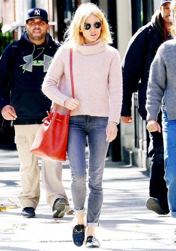 Sienna Miller wears a pink turtleneck, cuffed jeans, a red Mansur Gavriel bucket bag, and Gucci loafers