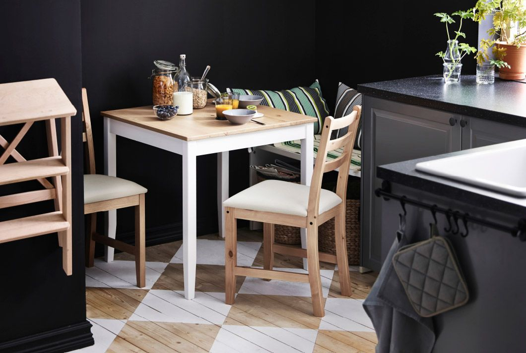 Small IKEA table with two chairs, laid for breakfast, in the corner ...