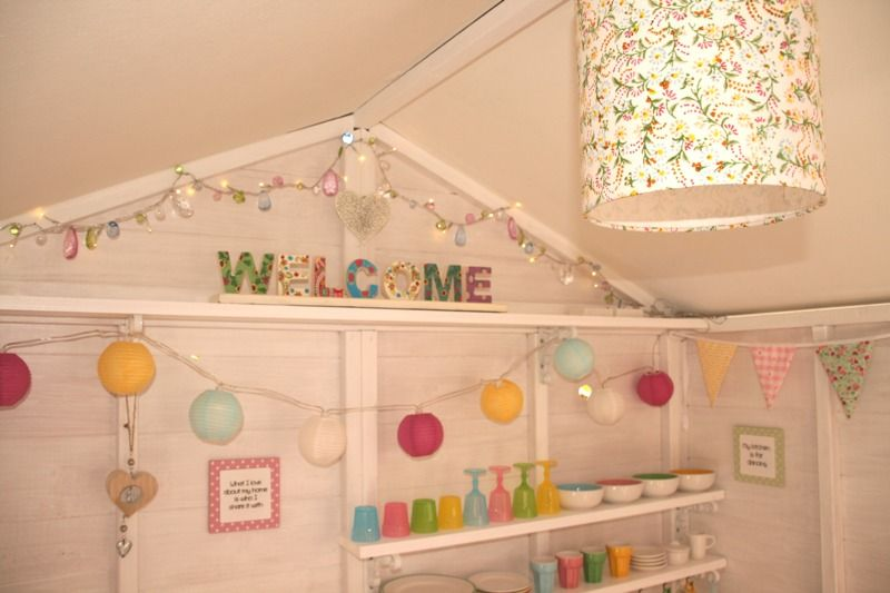 Decorated playhouse interior with lights shelves for Wooden wendy house ideas