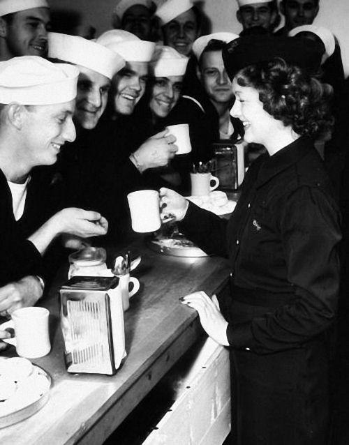 Myrna Loy serving coffee to American sailors