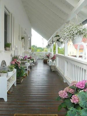 Wraparound Porch With Pots Planted In A Pink White And Green