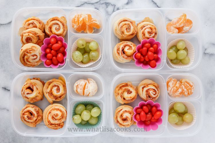 Pizza rolls, with tomatoes, grapes and oranges.