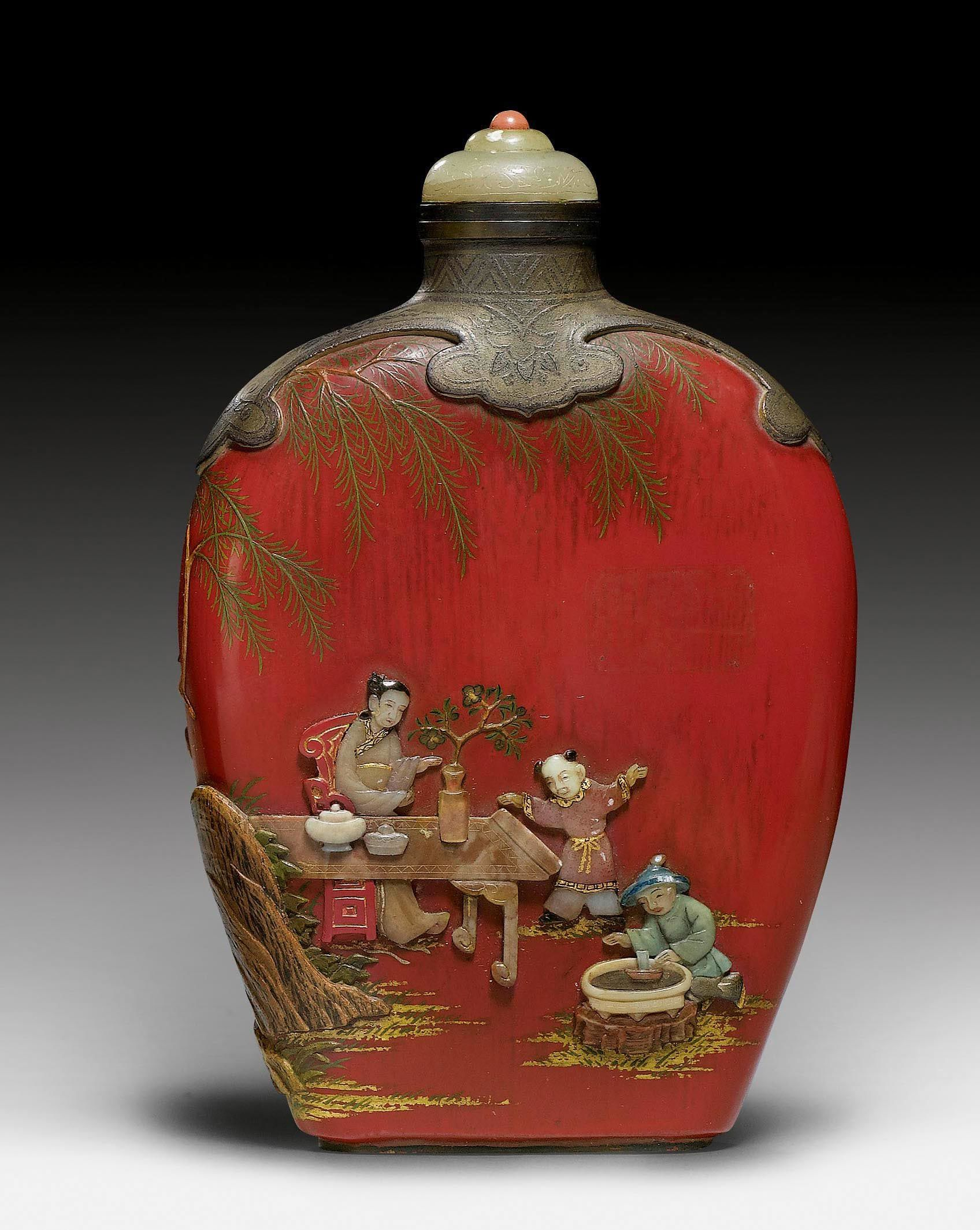 A FINE RED PAINTED WOOD SNUFF BOTTLE WITH STONE INLAYS. China, height 8.7 cm. Qianlong mark at the base. Matching stopper. China, H 8,7 cm. Flattened ovoid timber vials, painted red, with stone and wooden coverings. In a garden boy pleasure under the care of two women with the planting of Penjing Basin and insertion of flower bouquets. To this end, tables and chairs, where refreshments will also place outdoors under a tree. Fine details are painted and partly heightened with gold. The…