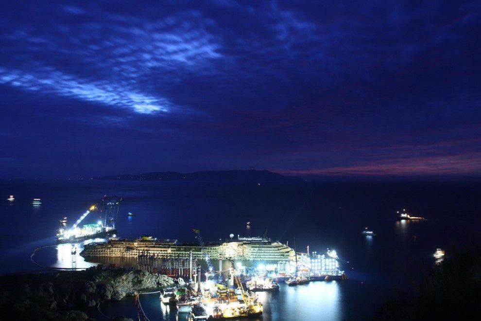 Dopo 19 ore di lavoro, le operazioni di parbuckling della Costa  Concordia sono state completate. Le primi luci dell'alba hanno  illuminato con gradazioni diverse di blu e di arancio il relitto emerso  dal mare