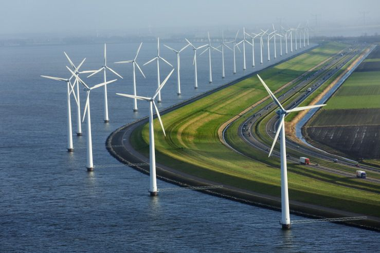 windmills generate electricity adjacent to the dike in the dutch ...