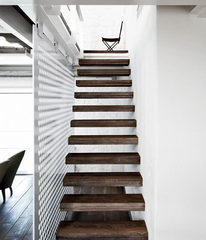 The upper level of the 5,300-square-foot space is accessed via a slender stair with reclaimed-wood treads.    Photo by Wichmann + Bendtsen.